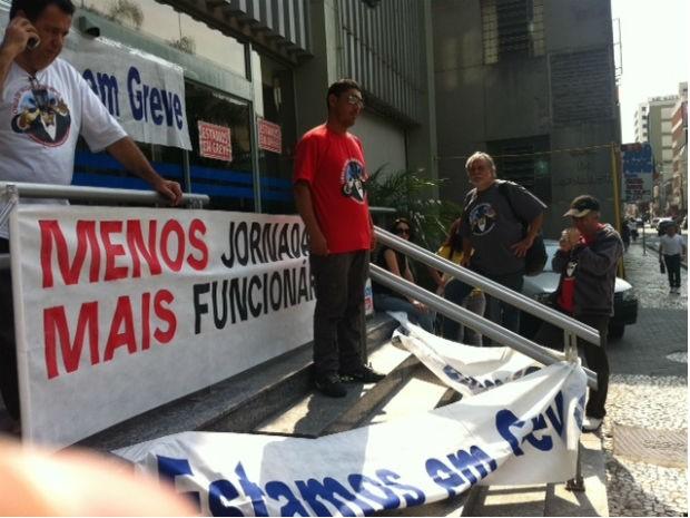 Bancários colocam as faixas nas agências na manhã desta terça-feira (18) (Foto: Marcelo Rocha / RPC TV)