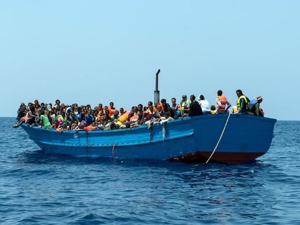 Imigrantes são vistos em um barco de madeira antes de serem resgatados no Mar Mediterrâneo. Mais de 190 mil imigrantes desembarcaram na Europa este ano, e mais de 2 mil morreram durante tentativas de travessia (Foto: Gabriele Francois Casini/MSF/via AP)