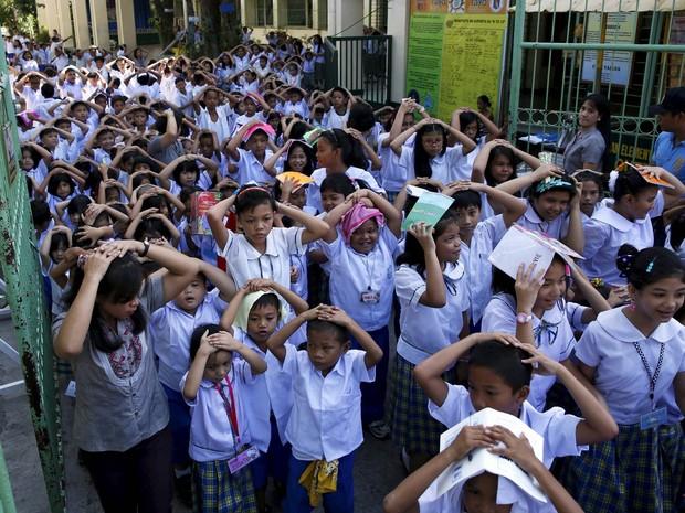Crianças filipinas saem com as mãos na cabeça acompanhados por professores enquanto participam de uma simulação de terremoto no segundo dia de aula em uma escola de Paranaque, na região metropolitana de Manila (Foto: Erik de Castro/Reuters)