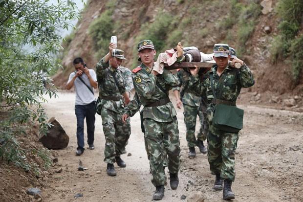 Equipes de resgate retiram sobrevivente de área afetada por terremoto em Ludian, na China, neste domingo (3) (Foto: AFP)