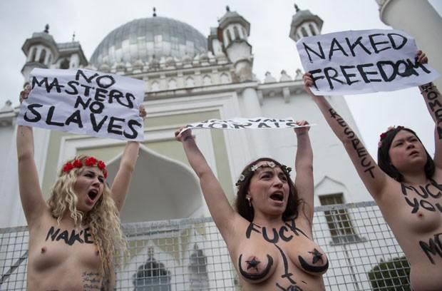 Jovens mostram os seios em protesto em frente a mesquita de Berlim, na Alemanha (Foto: Johannes Eisele/AFP)