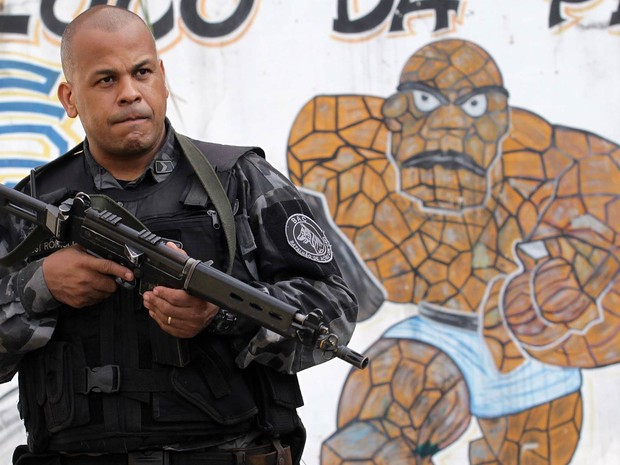 Com fuzil à mão, policial do Batalhão de Ações com Cães patrulha área da Vila Kennedy, na Zona Oeste do Rio, durante ação de ocupação da polícia (Foto: Marcos de Paula/Estadão Conteúdo)
