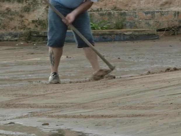 Depois que água baixou, moradores retiram lama das casas (Foto: Reprodução/TV TEM)