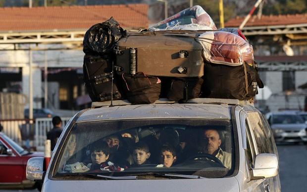 Por causa do conflito, família síria foge para o Líbano. (Foto: Hassan Ammar/AP)