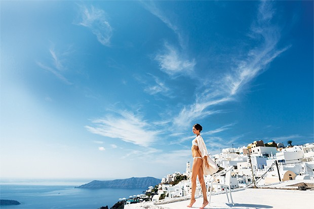 Sexy brunette female bride in lingerie in Santorini with sea and mountains in background (Foto: Getty Images/iStockphoto)