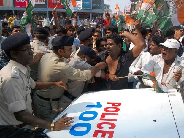 Ativistas discutem com policiais nesta quarta-feira (12) durante manifestação contra a morte de mulheres após esterilizações em massa na Índia (Foto: AFP PHOTO/STR)