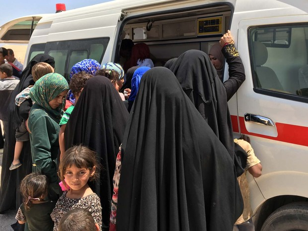 Mulheres e crianças iraquianas deslocadas fazem fila para receber remédios distribuídos pela Cruz Vermelha no campo recém aberto de Amriyat al-Fallujah, a 50 km a sudeste de Bagdá (Foto: JEAN MARC MOJON / AFP)