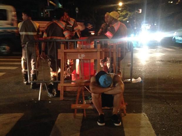 Rapaz passa mal e usa cone da CET para descansar no carnaval na Vila Madalena (Foto: Glauco Araújo/G1)