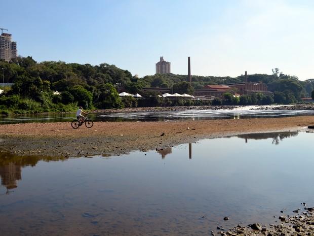Aposentado aproveita baixa vazão do Rio Piracicaba nesta sexta-feira (9) e anda de bike (Foto: Fernanda Zanetti/G1)