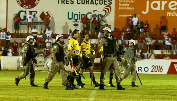 Gabriel Murta sai de campo escoltado após jogo entre Tricordiano e Tupi-MG (Foto: Reprodução Premiere)
