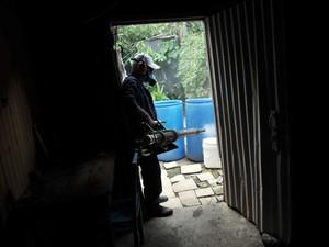 Na Costa Rica, funcionário faz fumigação de uma casa para eliminar possíveis criadouros do mosquito da dengue (Foto: AFP Photo/Hector Retamal)