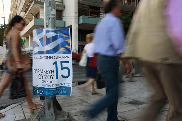 Gregos passam por propaganda eleitoral em rua de Atenas nesta quarta-feira (13) (Foto: AFP)