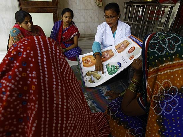 Profissional da saúde fala sobre câncer do colo do útero para mulheres em Mumbai (Foto: Rafiq Maqbool/AP)