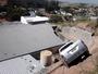 Caminhonete sem freio desce ladeira e quase cai sobre telhado de fábrica