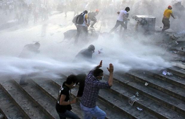Pessoas correm enquanto a polícia dispara um canhão de água no parque Gezi, em Istambul, neste sábado (15) (Foto: Murad Sezer/Reuters)