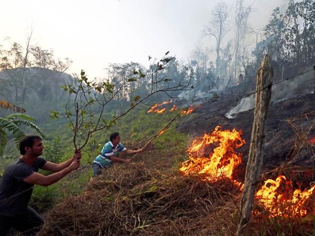 Júlio Adans Marchiori Filho, de 64 anos, e seu filho, Ricardo, de 44 anos, tentam conter o fogo que chegou ao seu terreno na cidade de Secretário, na região serrana do Rio de Janeiro, nesta quinta-feira (Foto: Wilton Junior/Estadão Conteúdo)