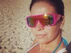 Com óculos grande, Solange Gomes corre na areia da praia