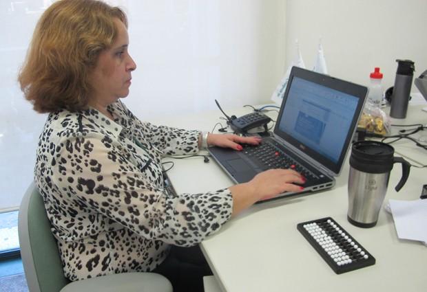 Marcia Costa trabalha há seis anos da Light. Nos corredores, há sinalizações em braille para que os funcionários deficientes visuais saibam onde estão localizadas suas mesas (Foto: Cristiane Cardoso / G1)