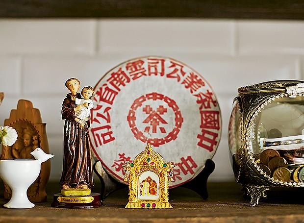 Na estante da sala, a imagem de Santo Antônio divide espaço com prato decorativo chinês e miniatura de templo budista comprado na Índia (Foto: Victor Affaro/Editora Globo)