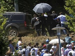 Seguranças usam guarda-chuvas para proteger o premiê sérvio, Aleksandar Vucic, após protestos com pedras na cerimônia de 20 anos do massacre de Srebenica (Foto: Antonio Bronic/Reuters)