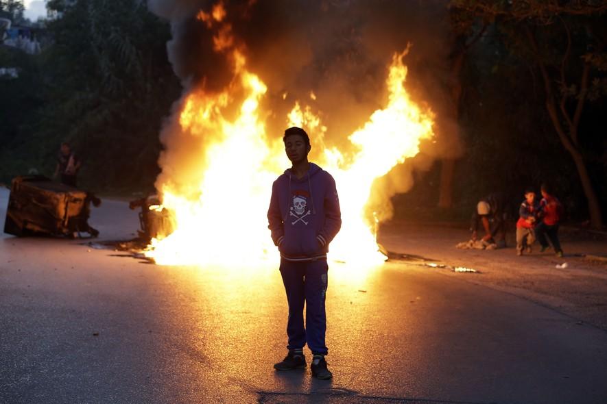 Jovem cigano protesta em Atenas, Grécia. Governo grego tentou remover famílias ciganas de uma área ocupada ilegalmente, e população reagiu fazendo barricadas e enfrentando a polícia. Após protestos, governo e ciganos chegaram a um acordo