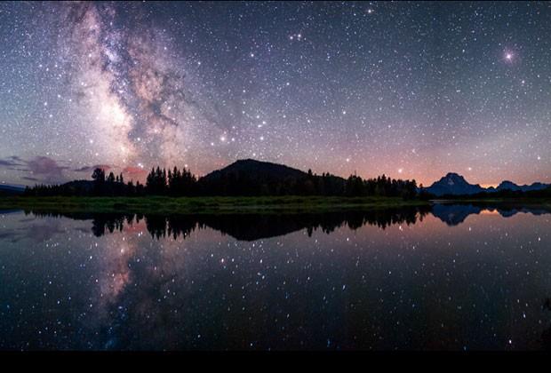 Esta fotografia mostra a Via Láctea refletida na curva Oxbow do rio Snake, no Parque Nacional de Grand Teton, EUA (Foto: David Kingham/BBC)