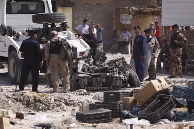 Policiais inspecionam destroços de carro usado em atentado em mercado de Basra, neste domingo (9) (Foto: AFP)