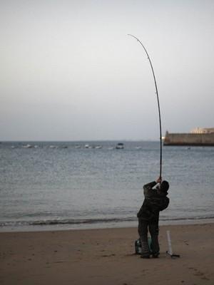 Pescador fisga peixe em região de Cádiz, no litoral da Espanha (Foto: Jon Nazca/Reuters)