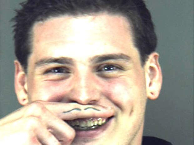 Ao posar para a foto depois de ser preso na Flórida (EUA) em 2010, um jovem fez gracinha e usou uma tatuagem em um dos dedos para criar um 'bigodinho' inusitado (Foto: Divulgação)