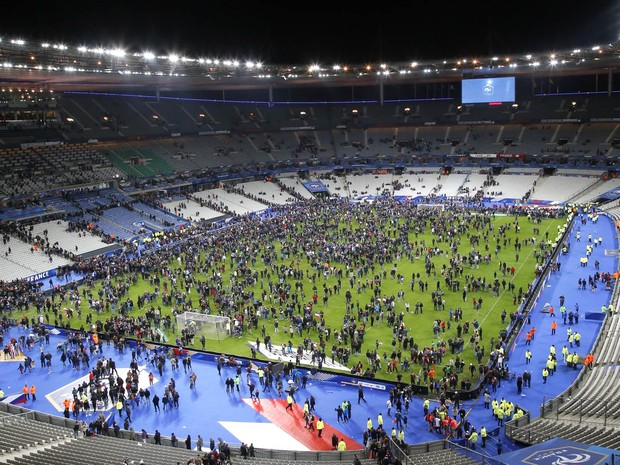 Gramado do Stade de France ocupado por parte do público após explosão. O estádio fica em Saint Denis, perto de Paris. Explosões foram ouvidas durante o jogo (Foto: Michel Euler/AP)