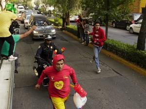 Durante o cortejo até a sede da Televisa San Ángel, neste sábado, fãs vestiram a fantasia do Chapolin Colorado e o gorro do Chaves para se despedir do comediante mexicano (Foto: Reuters/Carlos Jasso)