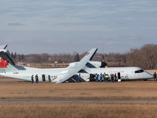 Investigadores analisam um avião de passageiros da Air Canada após pouso de emergência em Edmonton, no Canadá. O vôo 8481 saiu de Calgary, estava a caminho de Grande Prairie e transportava 71 passageiros, além de uma tripulação de quatro pessoas (Foto: Jason Franson/The Canadian Press/AP)