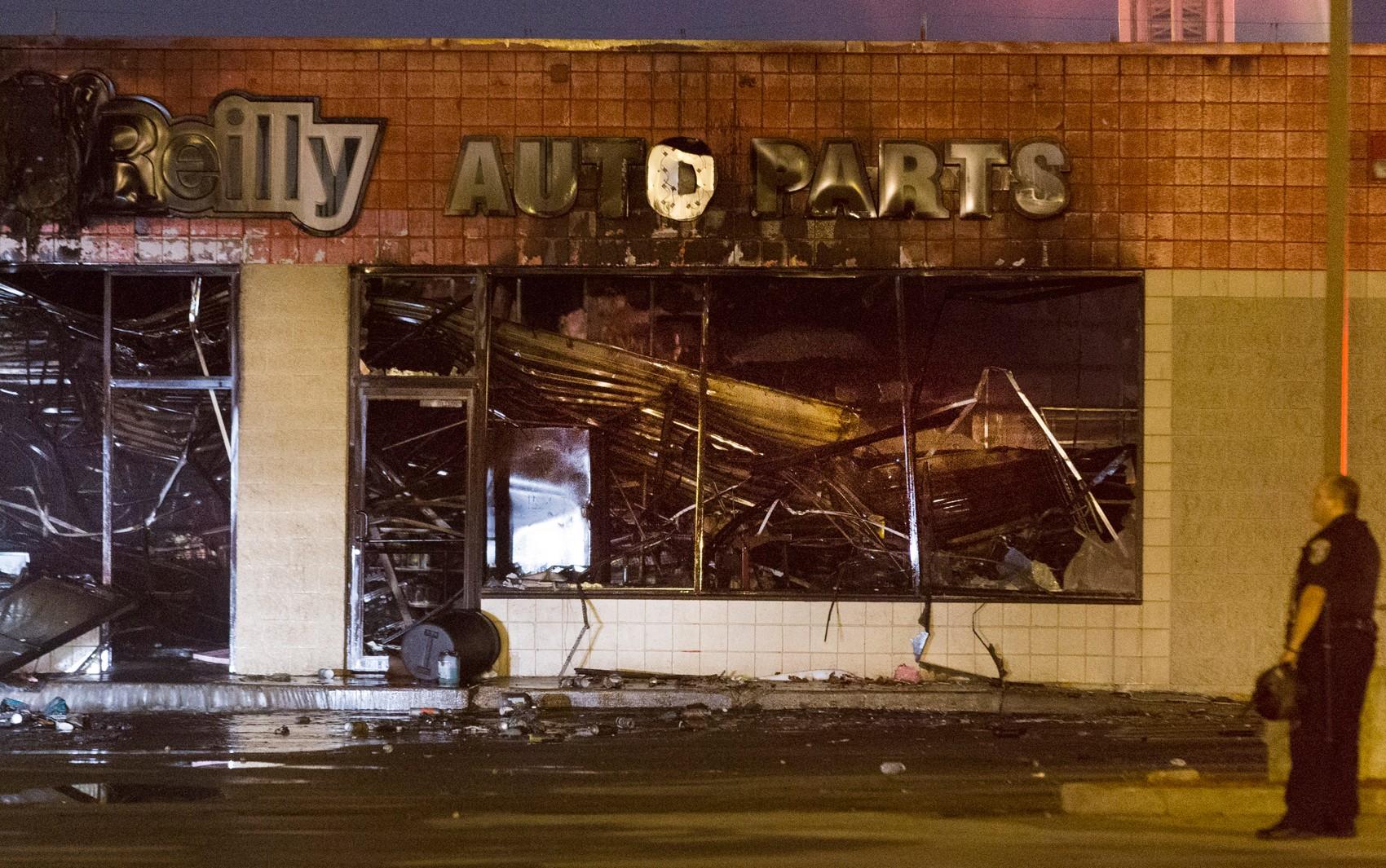 Policial vê fachada de loja destruída durante protestos na madrugada deste domingo (14)  (Foto: Mark Hoffman/Milwaukee Journal-Sentinel via AP)