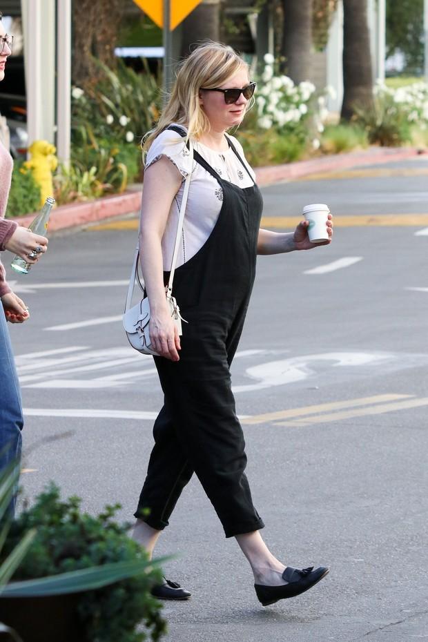 Kirsten Dunst exibe a barriguinha de grávida durante passeio com amiga (Foto: Backgrid)