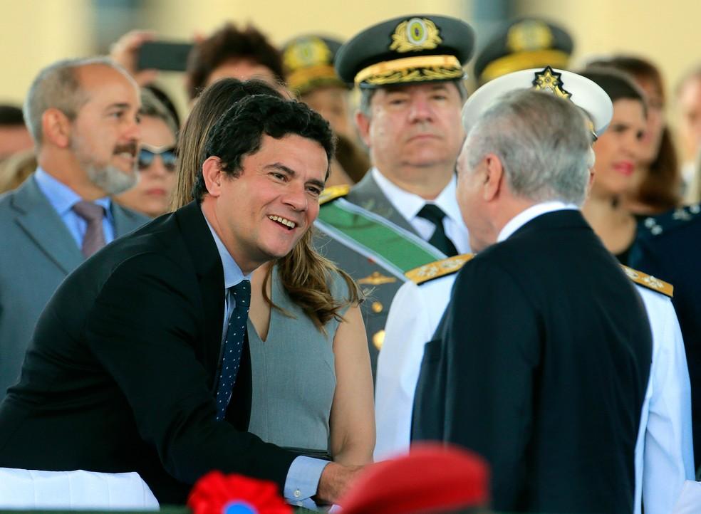 O presidente da República, Michel Temer (de costas à direita), cumprimenta o juiz federal Sérgio Moro na chegada à cerimônia em comemoração ao Dia do Exército, realizada no QG do Exército em Brasília (Foto: Dida Sampaio/Estadão Conteúdo)