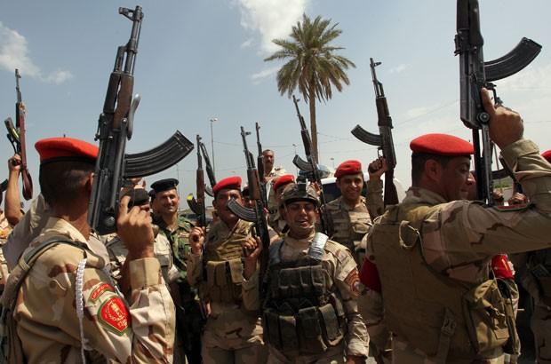 Tropas iraquianas cantam slogans contra o Estado Islâmico no Iraque e Levante (EIIL) enquanto recrutam voluntários para operação contra os jihadistas em Bagdá nesta sexta-feira (13)  (Foto: Ali Al-Saadi/AFP)