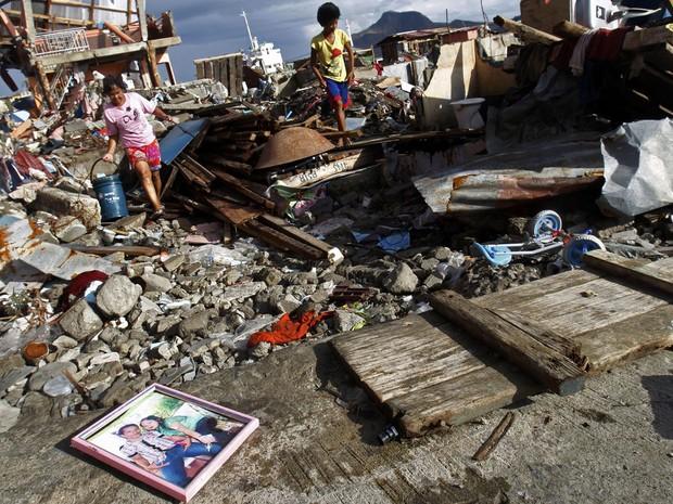 16/11 - Sobreviventes passam pelo retrato de uma família em meio aos escombros de uma comunidade em Tacoblan, na região central de Filipinas (Foto: Edgar Su/Reuters)