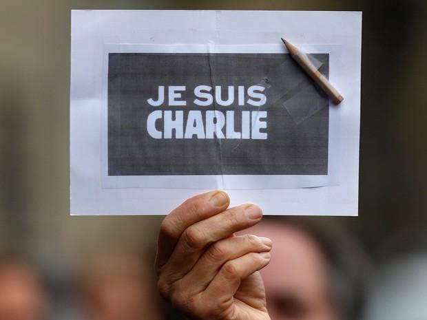 Uma pessoa exibe um cartaz com um lápis onde se lê 'Eu sou Charlie' durante um minuto de silêncio em Estrasburgo, na França (Foto: Vincent Kessler/Reuters)