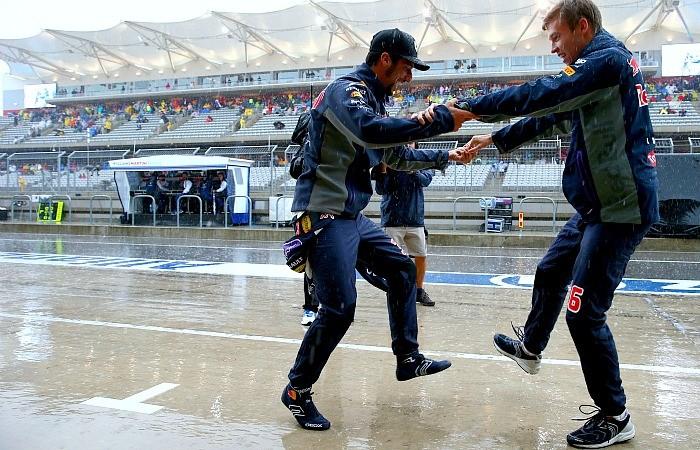 Daniel Ricciardo e Daniil Kvyat dançam no pit lane na chuva