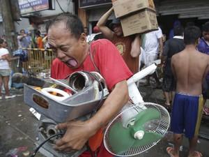 10/11 - Filpino carrega objetos que foram saqueados de uma mercearia em Tacloban nas Filipinas. (Foto: Aaron Favila/AP)