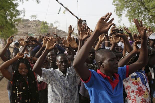 Nigerianos passam por inspeção de segurança antes de votar neste sábado (28) em Yola; suposto ataque islamita matou duas pessoas em local de votação (Foto: Sunday Alamba/AP)