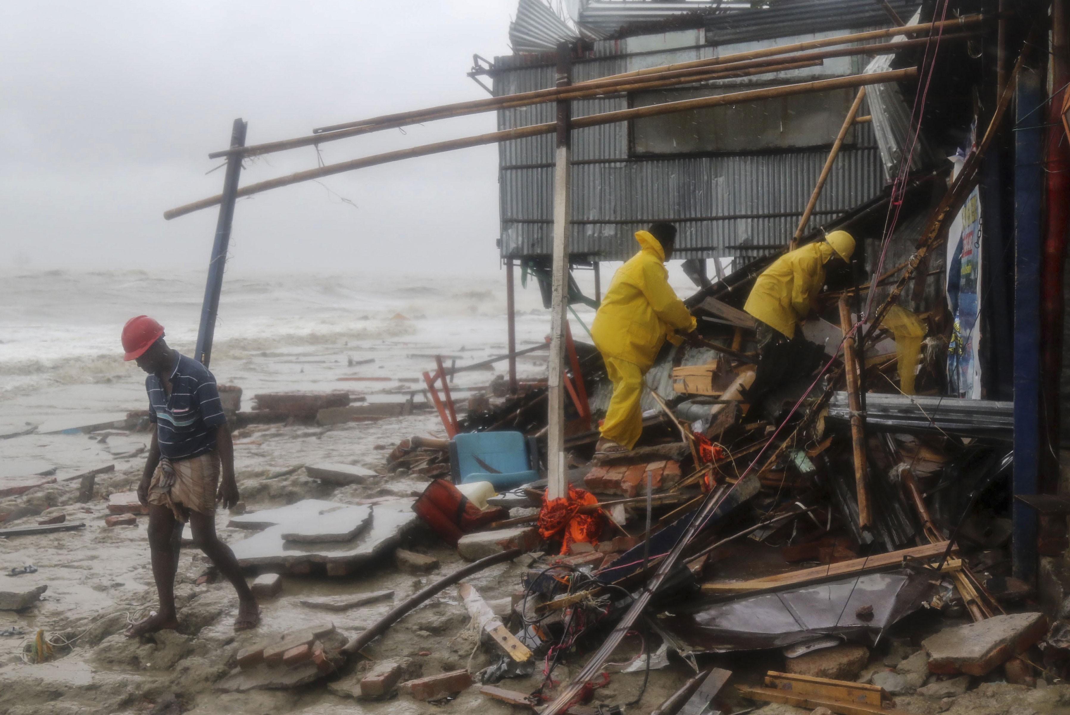Equipe de resgate procura por sobreviventes após passagem do ciclone Roanu, neste sábado (21).
