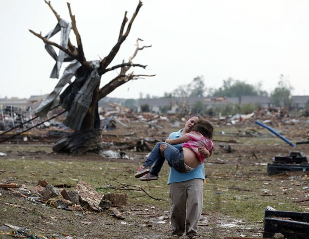 Mulher carrega criança em região próxima a escola atingida por tornado em Moore, Oklahoma (Foto: AP)
