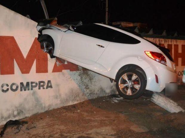 Carro de luxo bate em toco de madeira e fica pendurado em muro (Foto: Alisson Silva/ Edição de Notícias)