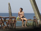 De biquíni, Daniele Suzuki toma água de coco na orla do Rio