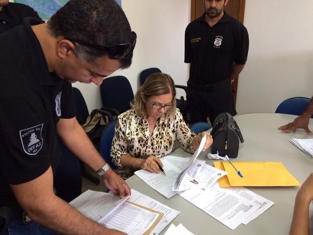 Imagem mostra delegada verificando documentos (Foto: Polícia Civil/ MT)