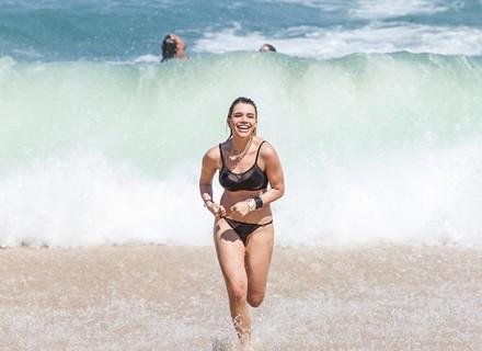 Belisa tira a roupa na praia e mergulha no mar só de lingerie