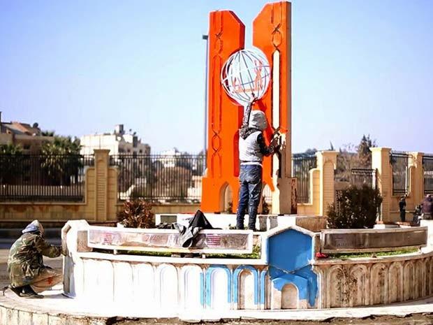 Imagem divulgada em abril mostra membros do Estado Islâmico pintando praça central em Raqqa, na Síria (Foto: Militant website via AP)