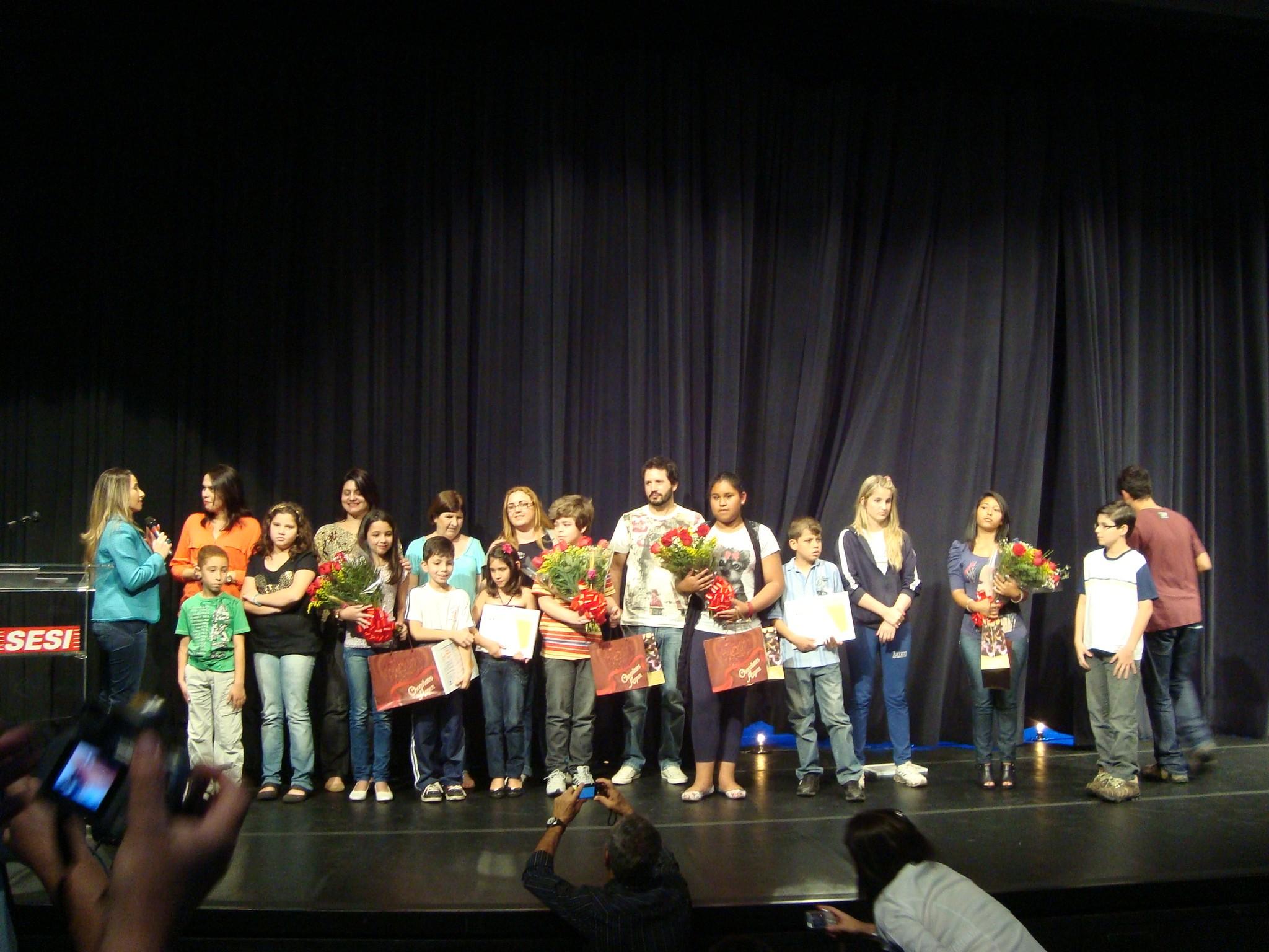 Professores e alunos junto no palco para receber prêmios do Concurso de Redação. (Foto: Deise Voigt / G1)