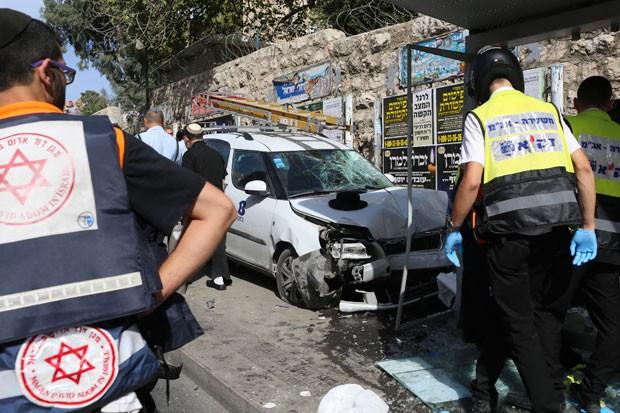 Policiais são vistos em local de ataque em Jerusalém nesta terça-feira (13); homem bateu carro contra ponto de ônibus e atacou pessoas com uma faca (Foto: Oren Ziv/AP)